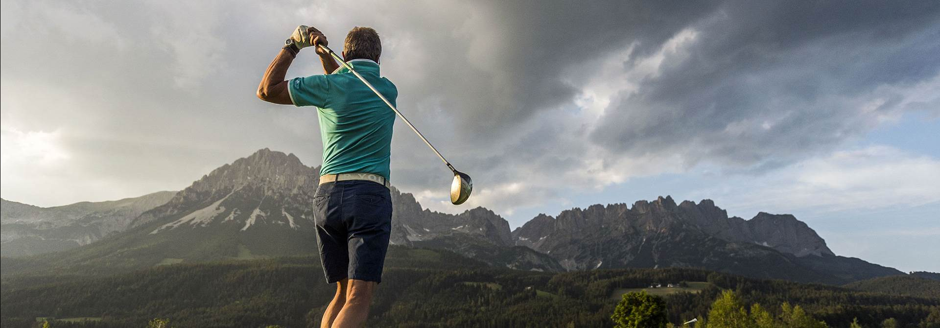 Golfer in front of a mountain panorama